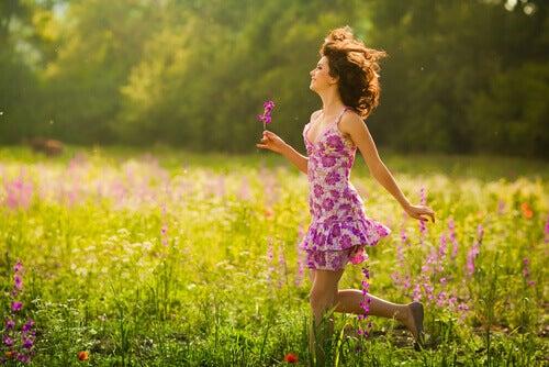 Mulher caminhando entre as flores sorridente e feliz