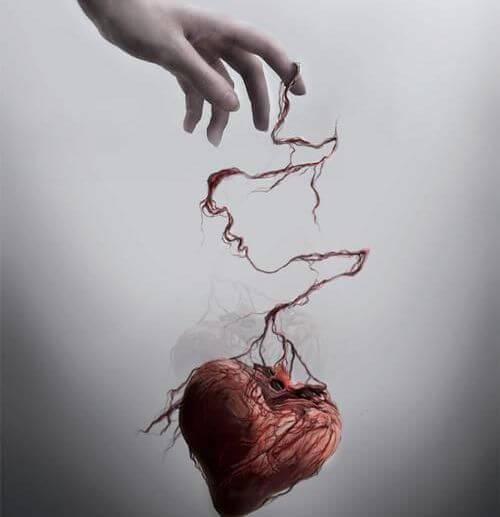 mão segurando coração maltratado por abusos