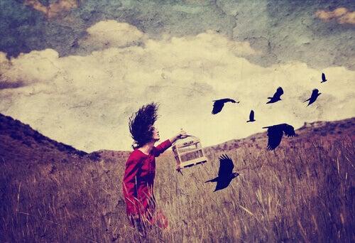 Mulher libertando pássaros e a sua essência