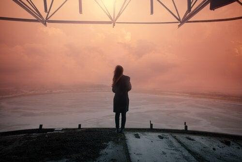 Mulher olhando o horizonte ao entardecer
