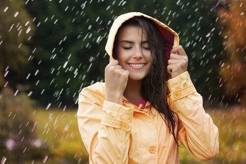 Mulher na chuva sentindo felicidade