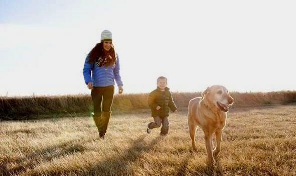 Mãe e filho passeando com seu cão