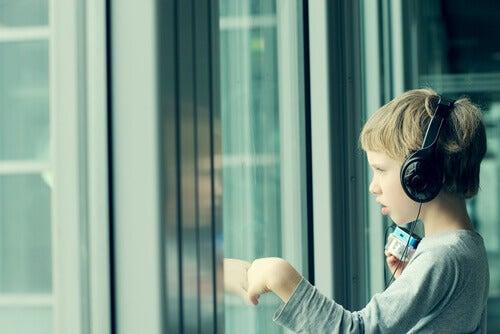 Menino com síndrome de asperger ouvindo música com seu fone