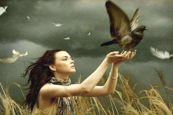 Mulher com pombo nas mãos