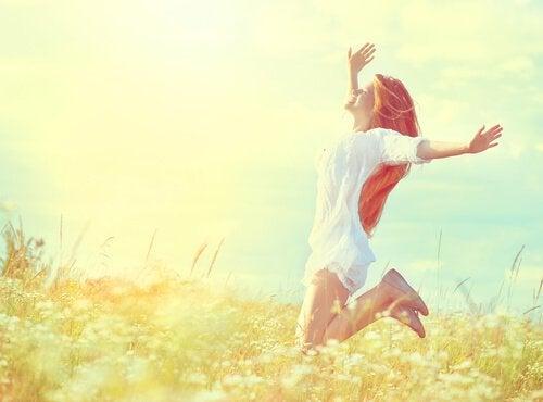 Mulher feliz saltando no campo