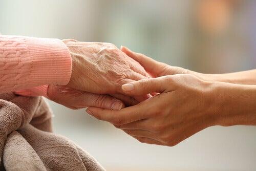 Mulher jovem segurando as mãos de uma pessoa mais velha