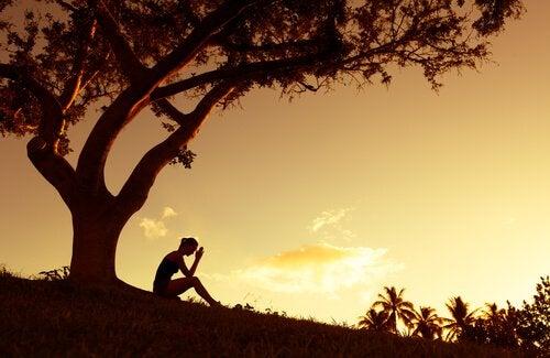 Mulher sentada embaixo da árvore