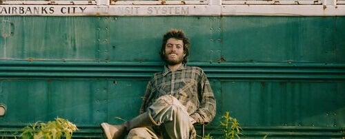 Christopher McCandless sentado apoiado em seu trailer