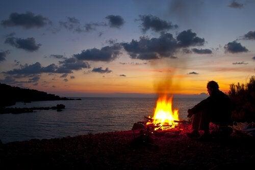 Homem ao anoitecer com fogueira na praia