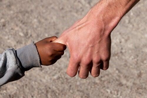 Mão de um menino negro segurando a de um homem branco