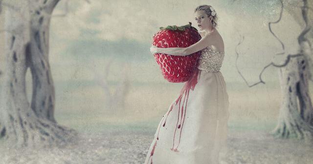 Mulher abraçada a um morango gigante