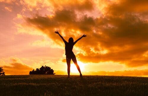 Mulher com os braços abertos vendo o por do sol