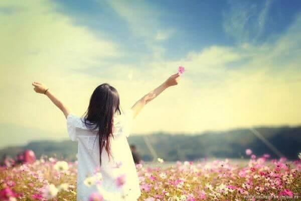 Mulher-com-uma-flor-na-mão-olhando-ao-infinito