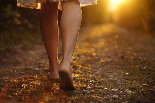 Mulher descalça andando por um caminho