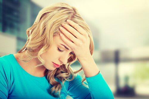 Mulher preocupada com a mão na testa