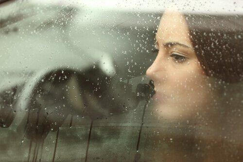 Mulher triste olhando pela janela do carro cheia de gotas