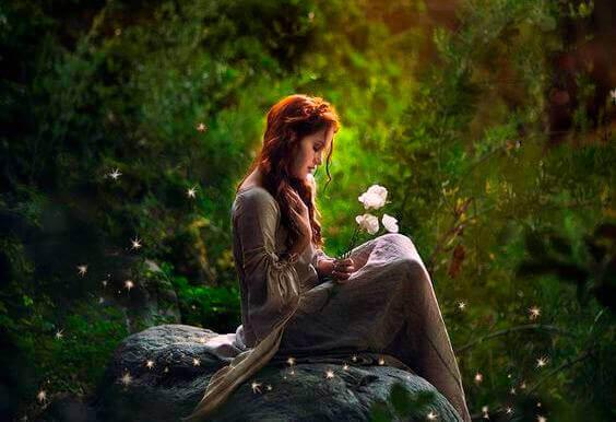 menina-em-bosque-segurando-flor