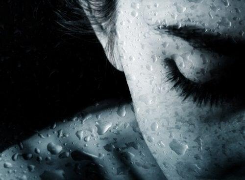 Mulher com os olhos fechados chorando