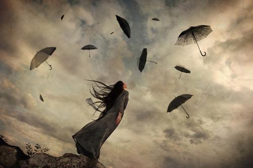 Mulher olhando para os guarda-chuvas voando no céu