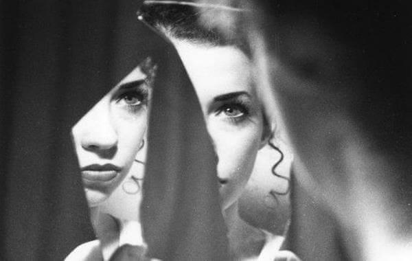 Mulher se olhando no espelho quebrado