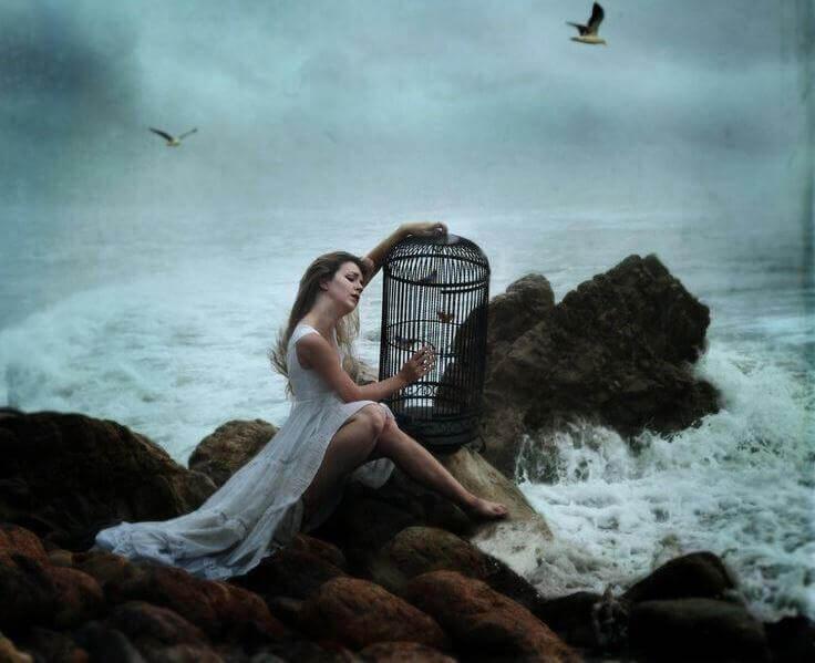 Mulher-sofrendo-sentada-ao-lado-do-mar