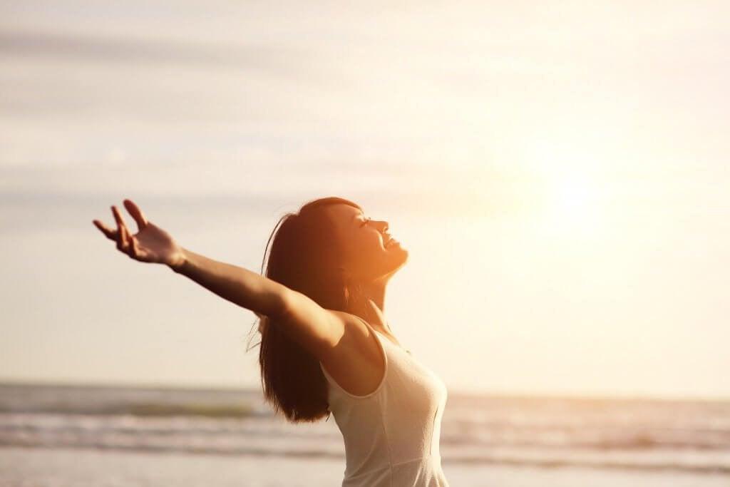 mulher_positiva_feliz_abrindo_os_bracos_para_o_sol_amanhecer