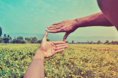 Mãos formando um quadrado selecionando uma parte da paisagem