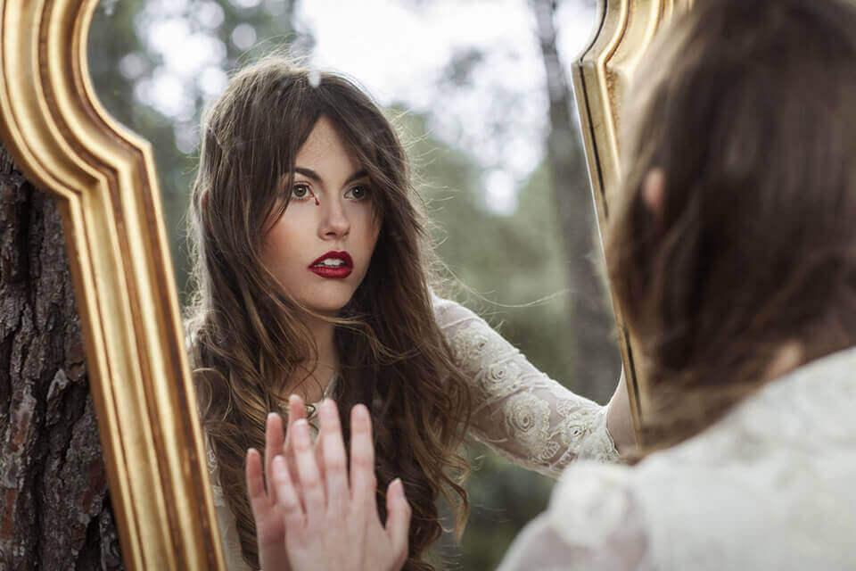Mulher se olhando no espelho com uma lágrima de sangue