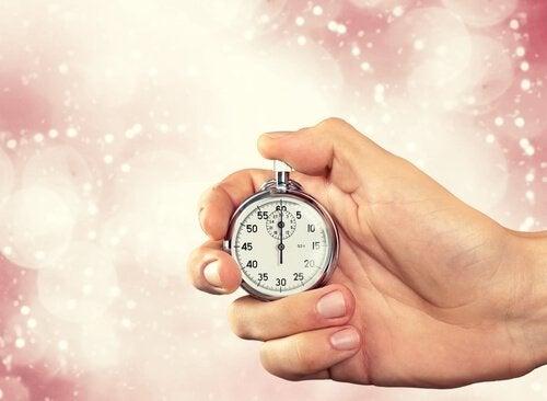 mão segurando um relógio