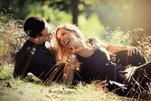 casal-sorrindo-deitado-na-grama-flertar
