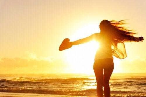 mulher-sozinha-na-praia-com-coracao-na-mao