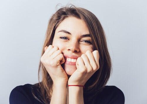 mulher-sorrindo-com-as-maos-no-rosto