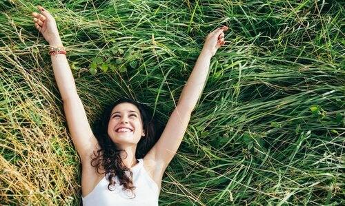 mulher-feliz-deitada-na-grama