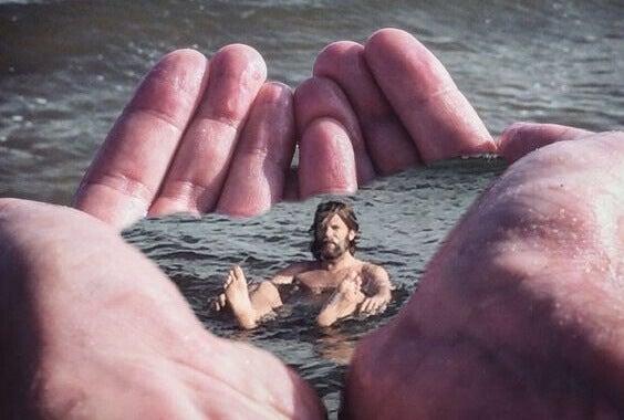 Homem boiando em água em mãos