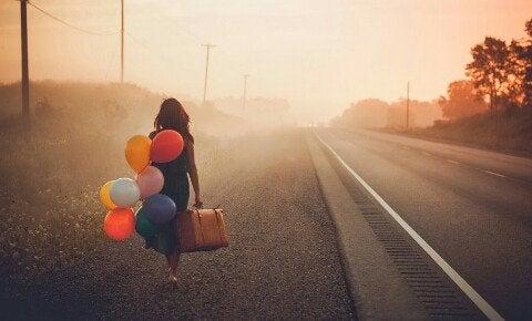 Mulher indo embora com balões