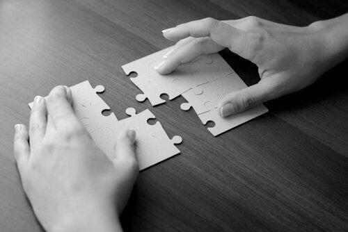 Mãos montando quebra-cabeças