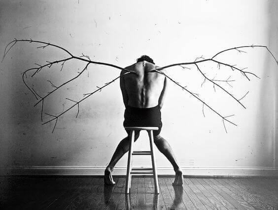 Homem com asas de galhos nas costas