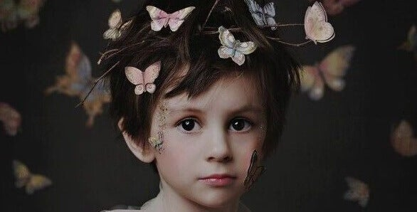 Menino com borboletas no cabelo