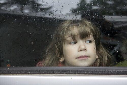 Criança olhando por janela de carro