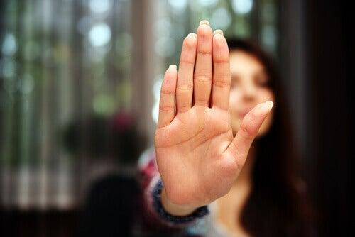 Mulher fazendo sinal de pare com a mão