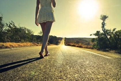 Mulher caminhando por estrada vazia