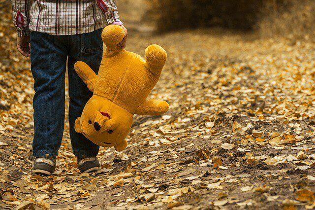 Criança caminhando com ursinho