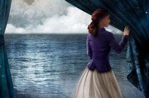 Mulher abrindo cortina diante do mar