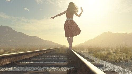 Mulher em trilho de trem refletindo para tomar a decisão certa