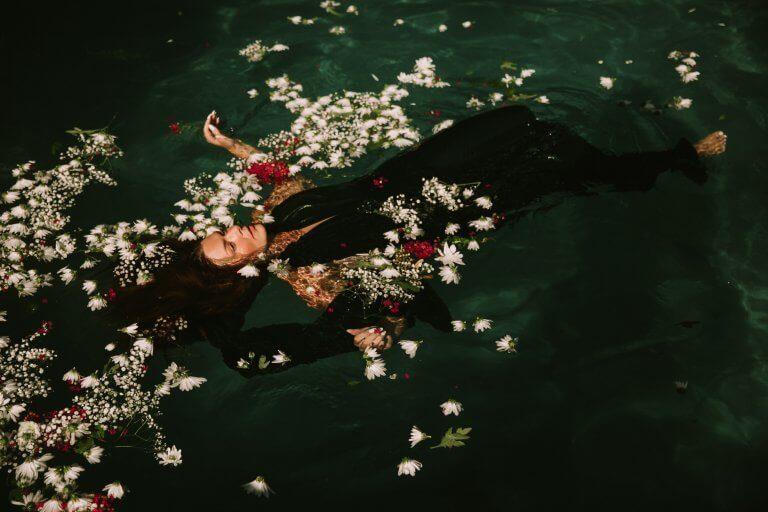 Mulher flutuando em piscina de flores