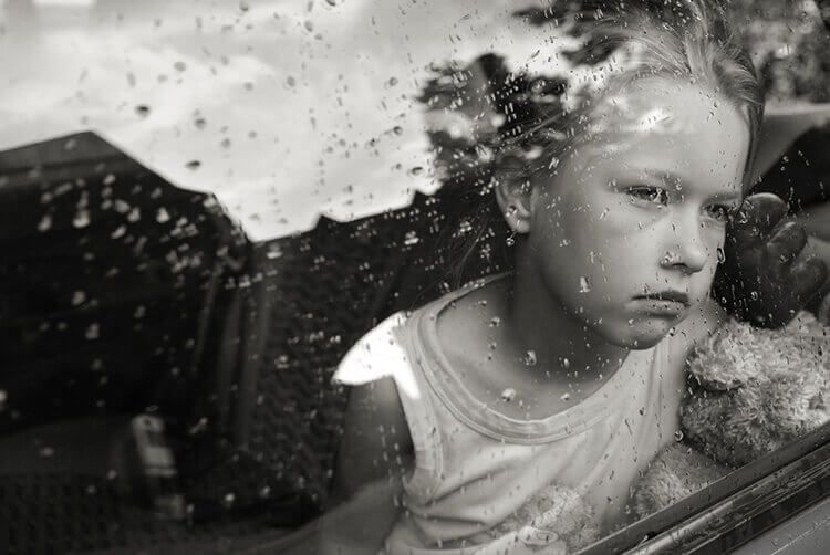 Criança observando a chuva