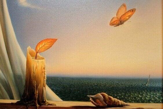 Vela e borboleta voando diante do mar
