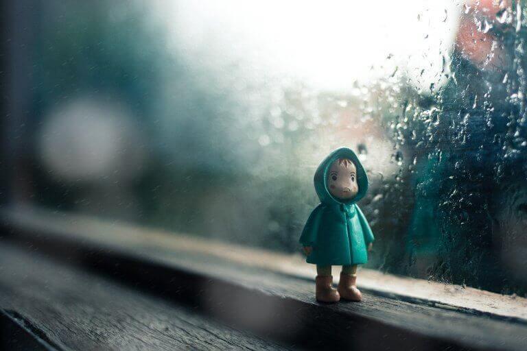 Boneco de criança na janela chuvosa