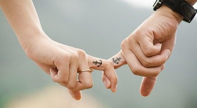 Dedos entrelaçados com tatuagens