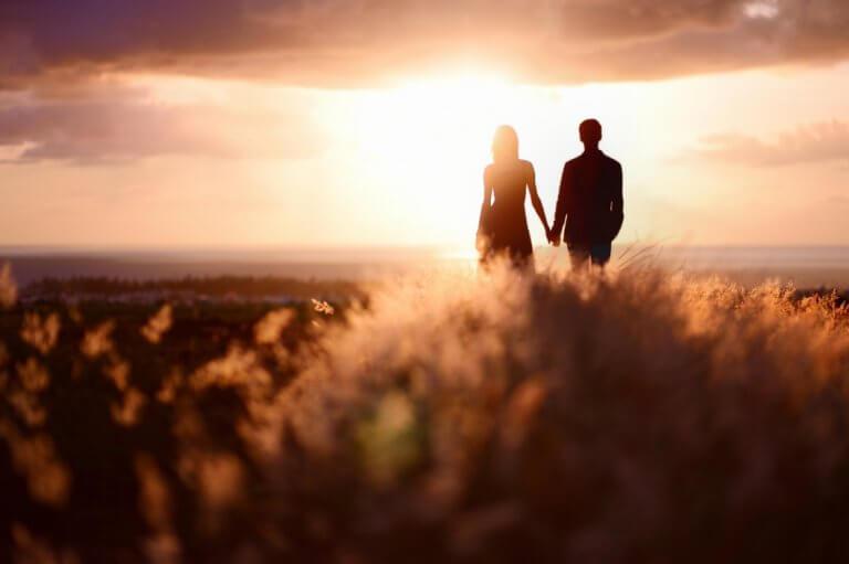 Casal de mãos dadas observando o pôr do sol